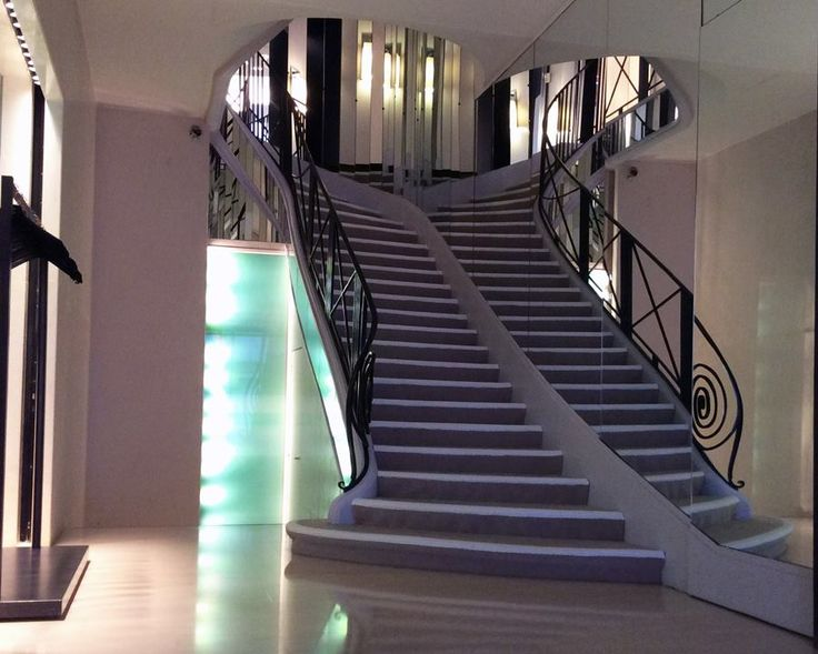 The classic mirrored staircase covered in a sand-like neutral carpeting, and wrought iron handrail, looks completely modern and beautiful.