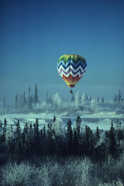 Hot air balloon hovers over a snowy landscape.
