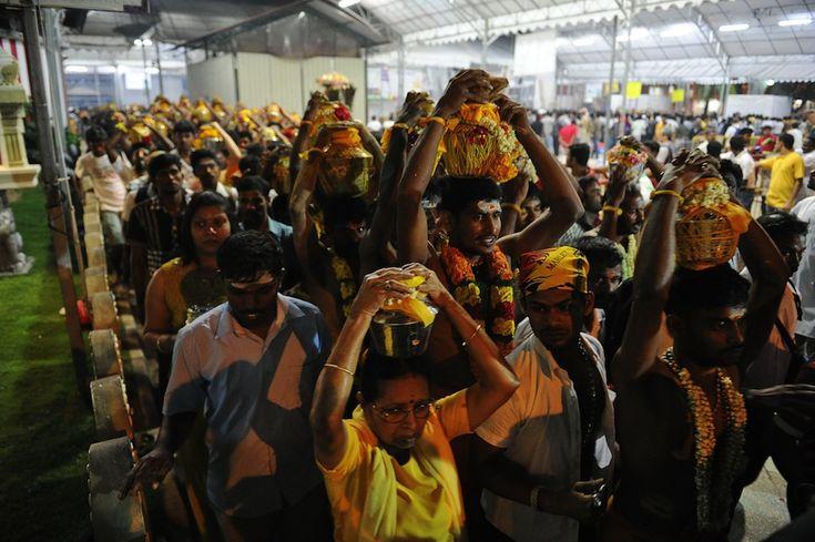 Gennaio 2014  IlPost - Singapore - Devoti indù portano dei vasi pieni di latte sulla testa, come parte di una processione per il festival indù Thaipusam, a Singapore. Il Thaipusam è celebrato durante la luna piena nel mese del calendario Tamil del Thai (gennaio/febbraio) e celebra il compleanno della divinità indù Murugan. (ROSLAN RAHMAN / AFP / Getty Images)