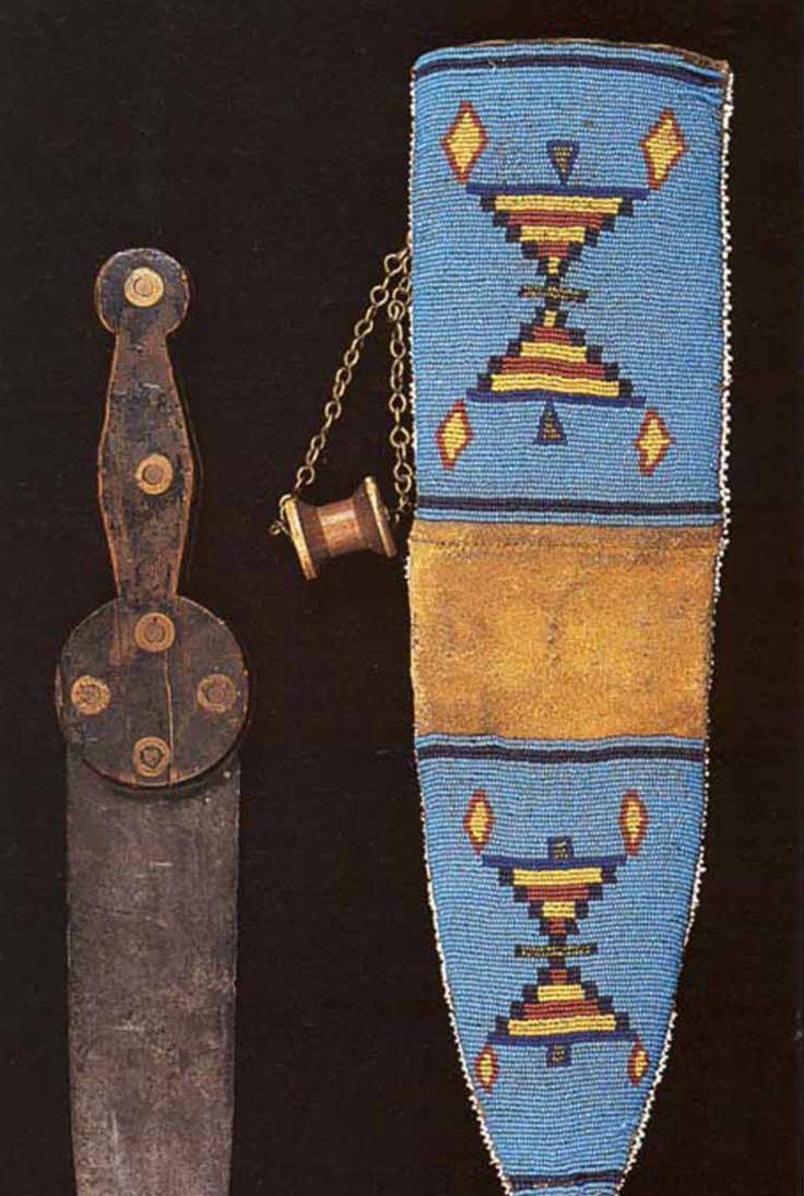 Нож и ножны, Черноногие. Деталь. Период 1850-1875. Коллекция Fenn. Нож Baldwin Hill, без клейма на клинке. Материалы: дерево, железо, стеклянный бисер, медный бисер, медная цепь (на ней катушка ниток для крепления к ремню), сыромятная кожа. Длина кинжала 14.5 дюймов, длина ножен 25,5 дюймов. Joe Rivera.   Splendid Heritage.