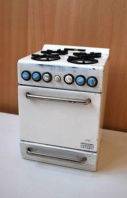 """Ancienne cuisinière jouet de la marque """"Arthur Martin """" de 19 cm de hauteur, 14 cm de largeur , 14 cm de profondeur. il y a un tiroir en bas qui s'ouvre , ainsi que la porte du four , ou il y a une grille pour déposer un plat."""