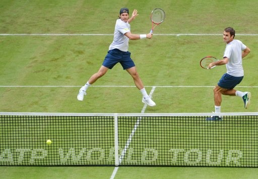 HALLE, GERMANY - JUNE 10: Tommy Haas (L) of Germany plays a forehand while Roger Federer of Switzerland looks on during their first round doubles match against Jurgen Melzer of Austria and Philipp Petzschner of Germany during day one of the Gerry Weber Open at Gerry Weber Stadium on June 10, 2013 in Halle, Germany. (Photo by Thomas Starke/Bongarts/Getty Images)
