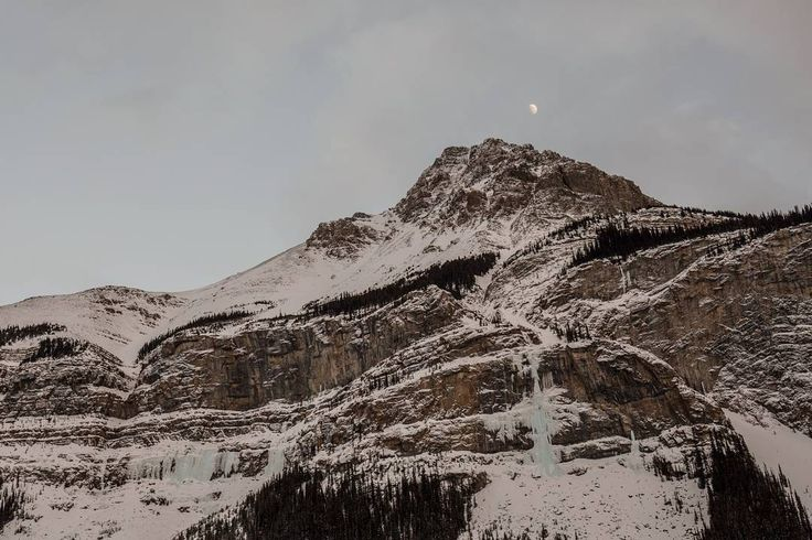 """""""Curtain Call"""" - As I drove down the Icefields Parkway after a day of climbing I couldn't believe my eyes. The sun was setting and the moon was right above the daunting climb known as """"Curtain Call"""" (WI6). The timing just seemed right. #MountainCultureElevated #ExploreAlberta #Rockies #winter #CanadianCreatives #exploreCanada #iceclimbing #ice #liveclimbrepeat #theclimbinglife #leavenomark #landscapes #winter #IceFieldsParkway"""