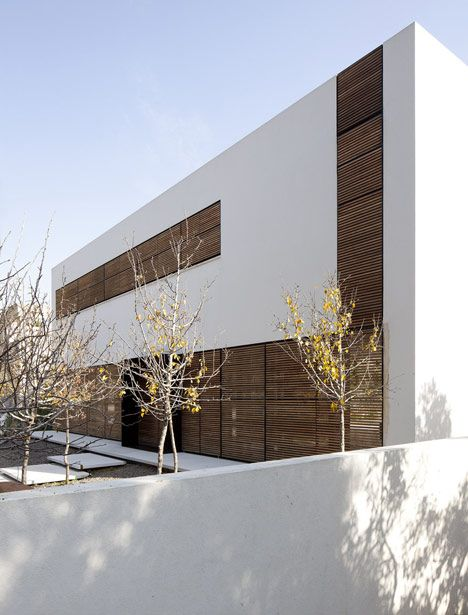 The louvred panels fold around two of the house's elevations and sit flush with the white-rendered walls to create a completely flat facade. They screen every window to moderate light and privacy levels inside the house.