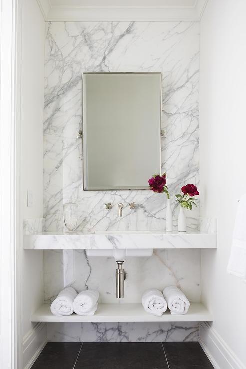 Stunning white powder room boasts a rectangular pi…