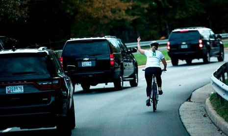 Jul Briskman gestures with her middle finger as a motorcade with Donald Trump departs Trump National Golf Course in Sterling, Virginia.