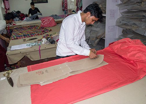 Cutting out the fabric for Tambah's trousers.