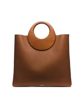 Infuse polished looks with an artful edge. Sculpted wooden handles crown this minimalist tote with a mod twist. Its roomy interior and buttery-soft leather design make this go-to carryall a refined statement piece.