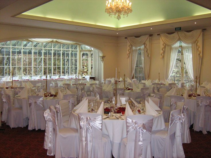 Wedding reception setup with white chair sash's, red rose petals and gold candelabras