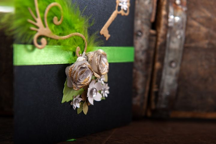 Petal fold style 21st Birthday invitation with gold key, flourish, green ribbon and feather with white flowers.