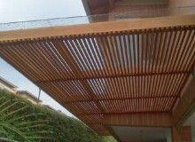 En madera Teca, vidrio templado, estructura metálica y acabados en Impranol.