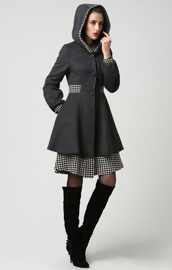 How pretty is this dark grey wool midi coat with accents of classic houndstooth fabric! From the trim on the hood and cuffs to the wide waistband to the second tier skirt, the houndstooth fabric adds a chic detailing to this truly feminine coat. Warm, as well as stylish, this coat is fully lined in polyester and also features long lantern style sleeves with point band cuffs, a two-layered skirt, deep side pockets and three fabric color button closure with snap closure on the bottom part of…