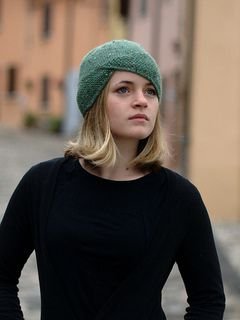 This cloche is alive with texture from the heathered yarn to the moss stitch brim and asymmetry. The construction of this Hat makes for a very interesting knit: beginning with a provisional cast on, stitches are worked onto the textured brim to create a seamless and stylish finish.
