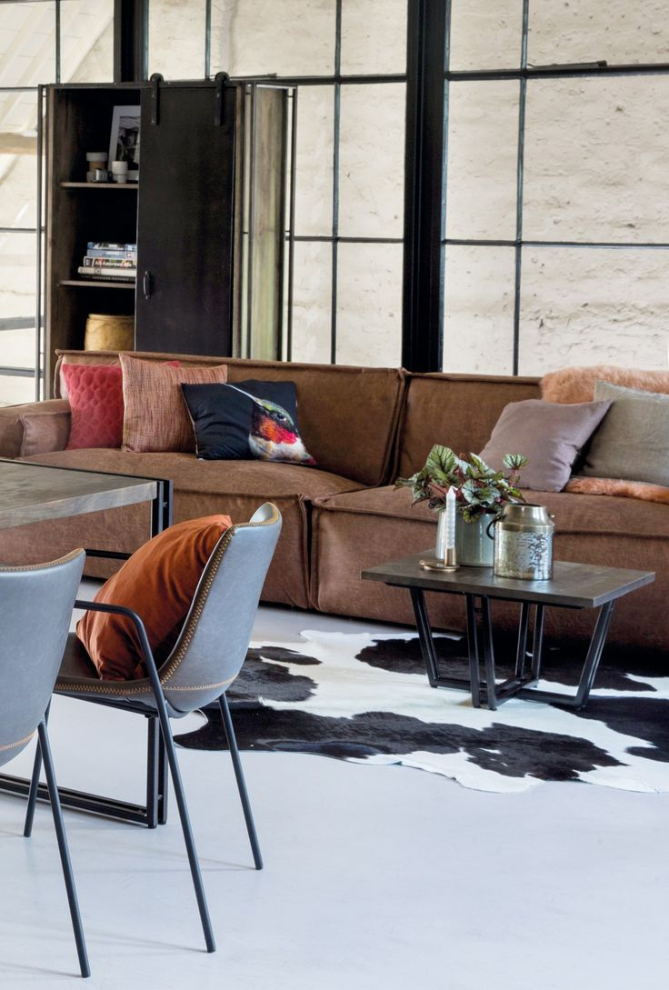 Trendhopper ● Wat een stoere woonkamer met bank Barletta in leer, het koeienkleed en salontafel Estrada van mangohout en zwart metaal onderstel.