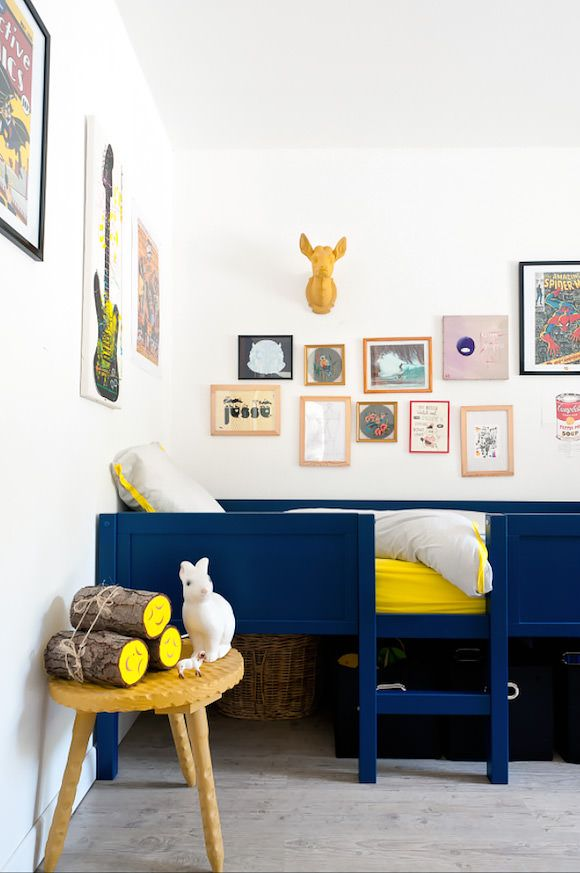 Contrasting colors make spaces come alive.  The midnight blue soothes and the vivid yellow energizes.   Love the grouping of the small artworks essentially giving you one large piece when you take a step back.
