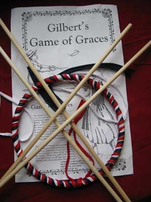 Faire Tyme Toys   Ribbon-covered hoop and sticks tossing game called Game of Graces (This is fun: figure out how to toss and catch a slippery hoop using two sticks)