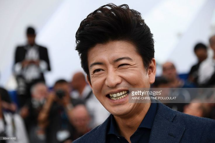 Japanese actor Takuya Kimura smiles on May 18, 2017 during photocall for the film 'Blade of the Immortal' (Mugen no Junin) at the 70th edition of the Cannes Film Festival in Cannes, southern France. / AFP PHOTO / Anne-Christine POUJOULAT