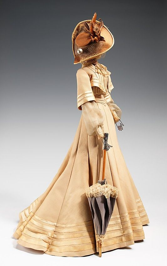"""1902 Doll"" Robert Piguet  (French, born Switzerland, 1901–1953) Designer: Paulette (French) Designer: Vedrenne (French) Designer: Fernand Aubry (French) Date: 1949 Culture: French Medium: metal, plaster, hair, silk, straw, cotton, feather, wood Dimensions: 31 1/2 x 14 in. (80 x 35.6 cm) Credit Line: Brooklyn Museum Costume Collection at The Metropolitan Museum of Art, Gift of the Brooklyn Museum, 2009; Gift of Syndicat de la Couture de Paris, 1949"