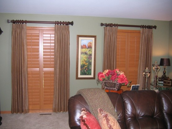 stained wood shutters adds a rich look with drapery panels to soften it up indoor shuttersbow window