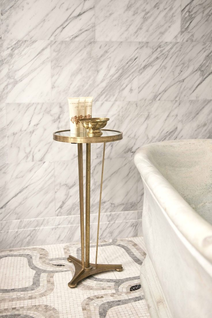 Global Views cigarette table. Marble tile walls look great with the patterned mosaic floor...The Greenwich Hotel #tub #marble #tile. For more inspiration, design tips and home decor ideas follow @SteinTeamNYC