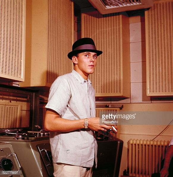 English singer Billy Fury (1940-1983) posed wearing a checked shirt and trilby hat whilst smoking a cigarette in a recording studio in 1963.