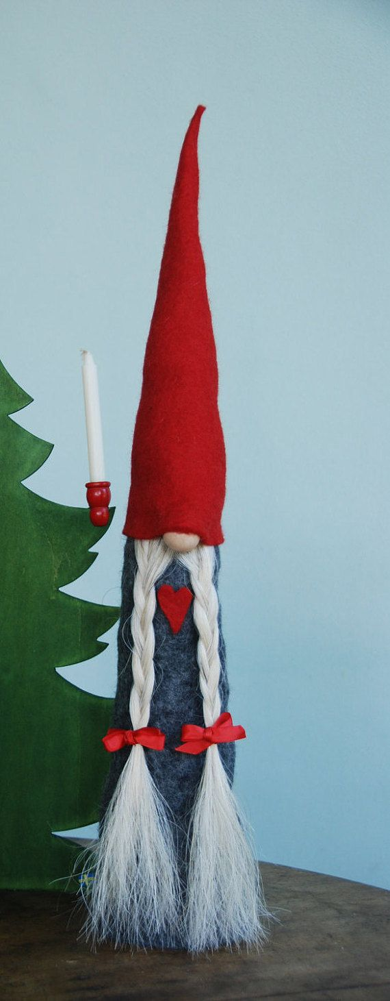A SwedishTomte is a small gnome that likes to take up residence near or under houses. He takes care of a farmers home and children and protects them from missfotune particular at night, when the house folk are asleep. This one of a kind Tomte is made of all natural materials, 100% wool felt for body and hat Horse tail hair beard Wood nose Stands on a 4 sturdy pine solid wood base Measures 23 in/58,5 cm tall with 4 in/7,5 cm diameter base.