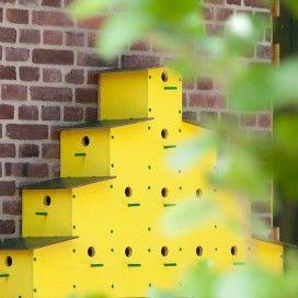 Flat van gestapelde en geel geverfde nestkastjes, met groene zitstokjes.