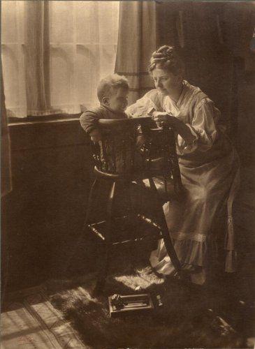 'Moeder en kind'. Een vrouw buigt zich over naar haar kind in de kinderstoel. Nederland, circa 1910.