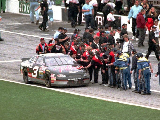 Crew members line up along pit road to congratulate Dale Earnhardt as the NASCAR legend finally wins his first Daytona 500 in 1998, 20 years after his first Daytona 500 start in 1979.