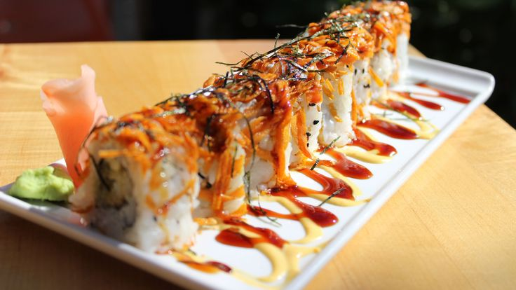 Eye Doctor Roll - Crispy shrimp and avocado topped with cream cheese, dried seaweed and tempura fried carrots on a bed of spicy mayo and topped with eel sauce.