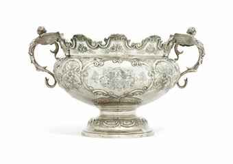 A VICTORIAN SILVER PUNCH BOWL MARK OF WALTER, JOHN, MICHAEL AND STANLEY BARNARD AND ROBERT DUBOCK, LONDON, 1899 Bombé shaped and on spreading circular foot, the body chased with scrolls and flowers, with everted notched shaped rim, applied with winged demi-caryatid handles, each side centred by a cartouche engraved with differing coat-of-arms, the interior gilt