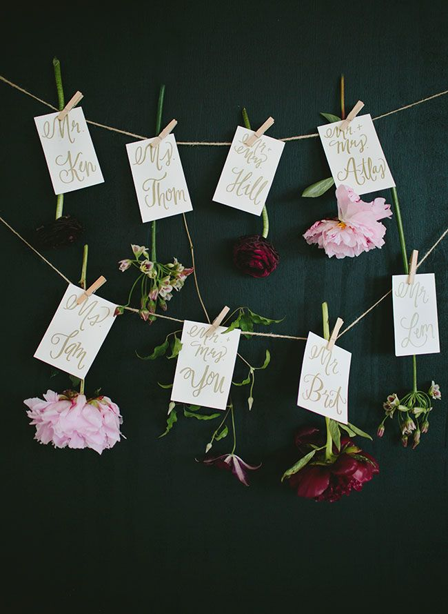 Floral escort cards on a clothesline
