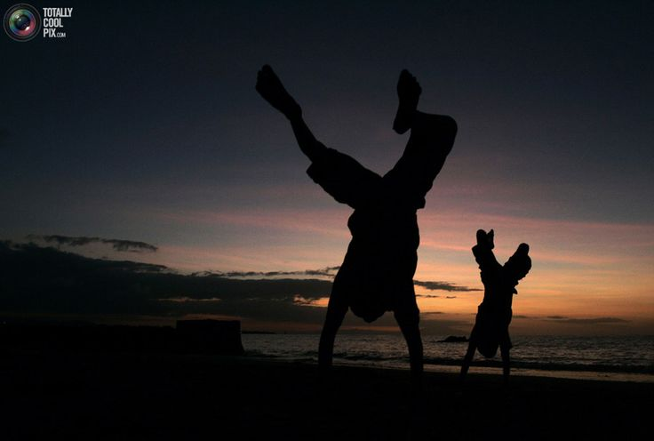 Adolescentes Timor Leste se vira para uma foto na praia,ao por do sol em Díli. REUTERS / Beawiharta