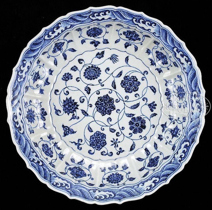 "BLUE AND WHITE MING STYLE PLATE 20th century, China. Lobated form. ""Heaped and piled"" decoration of floral scrolling with wave border. Unglazed base with ""Palm Eyes""."