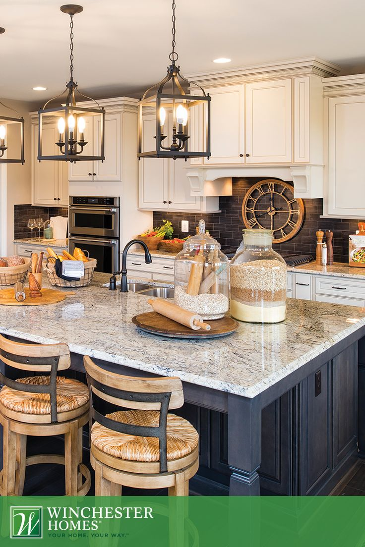 Timeless elegance is the key to the kitchen in the Raleigh model. Three chandeliers illuminate rustic kitchenware to give the room a farmhouse aesthetic with modern amenities. #InteriorDesign