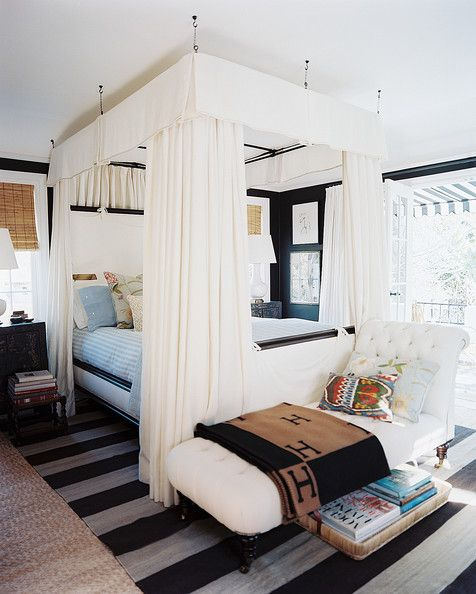 A white canopy bed and a tufted chaise in a bedroom with deep-brown walls  Details: Mediterranean-Traditional Bedroom  Keywords: Foot Of The Bed, Bedding, Canopy Bed, November 2012 Issue, Mark D. Sikes & Michael Griffin  (Source: Lonny)