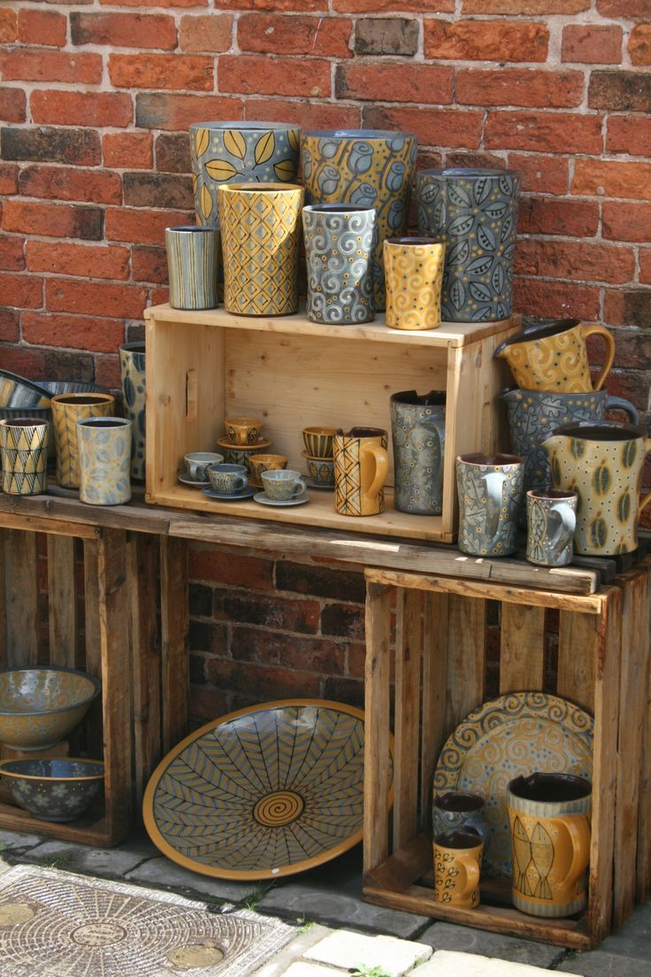 Great idea to display pottery at craft shows using crates. Gives pottery a different vibe. They've also done a great job of creating a collection around grey and yellow to group together and make an impact.