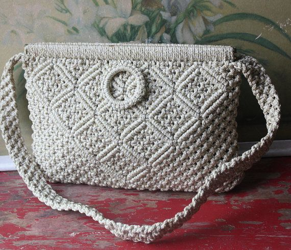 Classic crocheted handbag circa 1970s. Two pulls on each side to open the hinged opening. Cream colored interior lining. Single carrying strap.