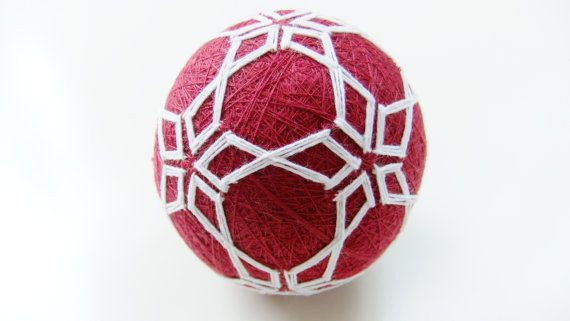 Red and white Temari ball A geometric pattern inspired by Seljuk architectural forms, also close to star/flower pattern Circumference: 26.5 cm / 10.4 Makes a sound when shaken (there is a small capsule of beads in it) Seen with two other balls in two of the images.