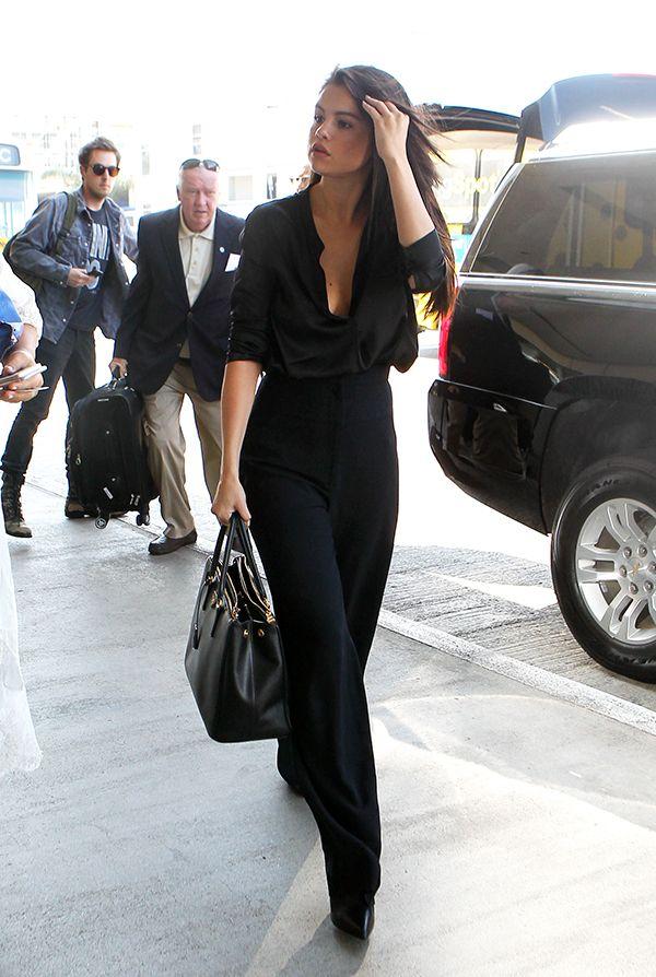 Selena Gomez usa camisa preta aberta com calça pantalona preta