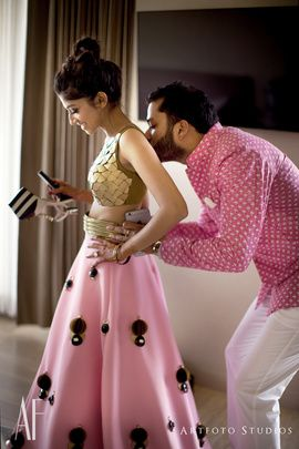 Sangeet Lehengas - Upasana & Karthik | Bride in a Shell Embellished Gold Blouse with a Pink Poofy Skirt with Embellishments and the Groom in a Pink and White Sherwani with White Pants #wedmegood #indianbride #indianwedding #bridal #lehenga #skirt #unique #different