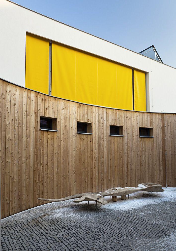 Modřínový obklad přízemí a výrazně žluté vnější zastínění prostorů v patře