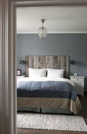 Stoere landelijke slaapkamer met bed van steigerhout. Mooie sprei op het bed, klein kleed op de vloer en opvallende hanglamp.