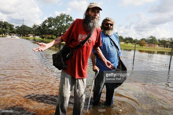 Flood survivors News Photo : Scott Padgett walks through his flooded...
