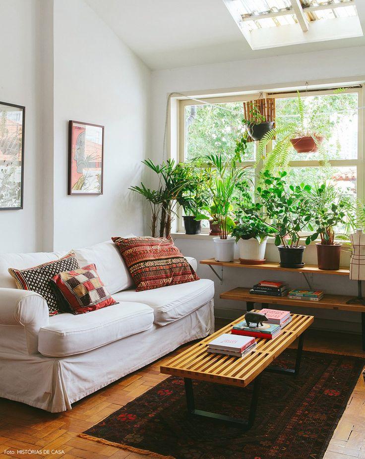 Sala de estar em um apê alugado, com sofá branco, prateleira com plantas na janela e tecidos étnicos