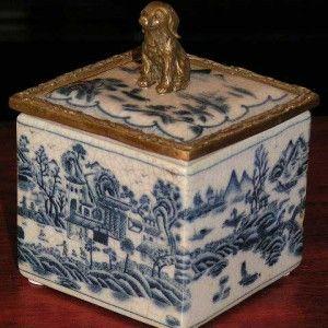 Prachtig blauw craquele sieraden doosje met Chinese afbeeldingen. Met bronzen rand en hondje bovenop.  Materiaal: keramiek / Brons  Afmetingen: Breedte: 9,5 cm Diepte: 9,5 cm Hoogte: 13 cm