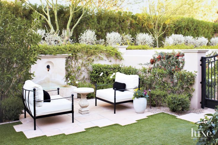 A custom carved limestone fountain with a decorative spout provides the centerpiece for yet another outdoor sitting area. The chair cushions wear outdoor fabric by Perennials.