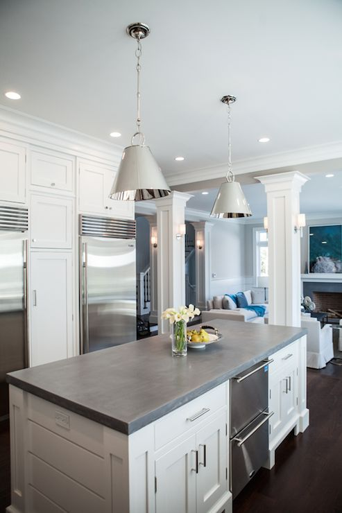 Gorgeous kitchen features a pair of Restoration Warehouse Altamont Metal Pendants illuminating paneled center island topped with concrete countertop accented with stainless steel stacked dishwashers across from wall of pantry cabinets framing twin Viking Refrigerators.