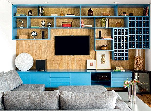 A designer de interiores Magda Marconi criou o móvel com múltiplas funções para a sala de TV. Nichos de tamanhos variados com acabamento de laca azul são fixados no painel de freijó. (Foto: Edu Castello/ Editora Globo)