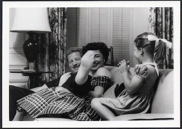 Danny Kaye, Sylvia Fine and young Dena sit on couch in living room, Danny stretching his foot toward Dena playfully.